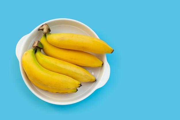青い背景の上の白いボウルにバナナの果実。