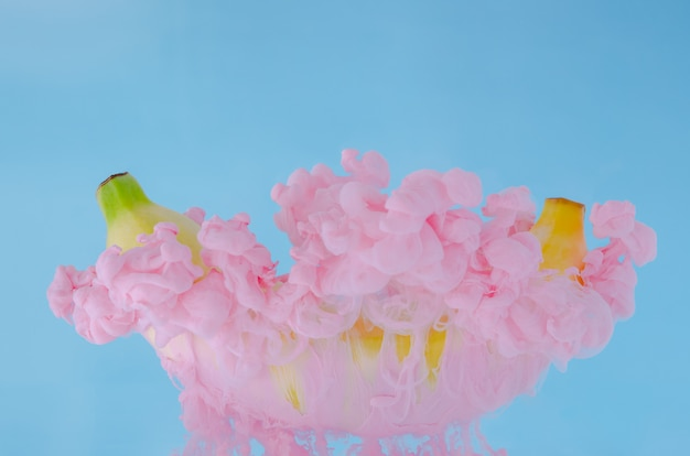 A banana fruit with partial focus of dissolving pink poster color in water on blue background.