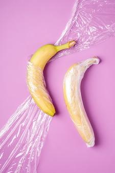 Фрукты банана, завернутые в стрейч-пластик на розовой поверхности