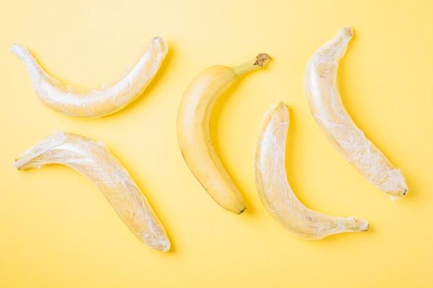 Плоды банана, завернутые в стрейч-пластик на желтой поверхности