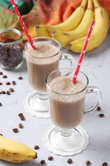 Banana latte with spices in two glasses and fruit around on light gray background