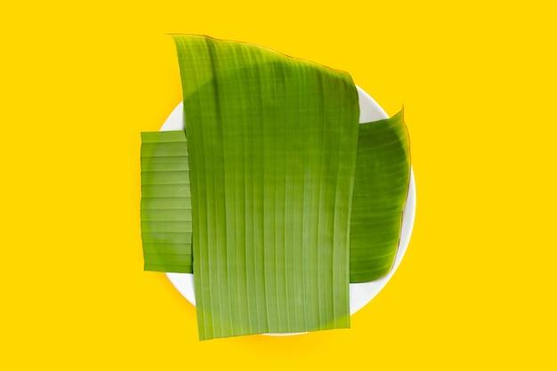 Банановый лист в белой тарелке на желтом фоне.