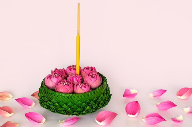 Banana leaf krathong decorates with pink lotus flowers and petals for thailand full moon or loy krathong festival on pink background.