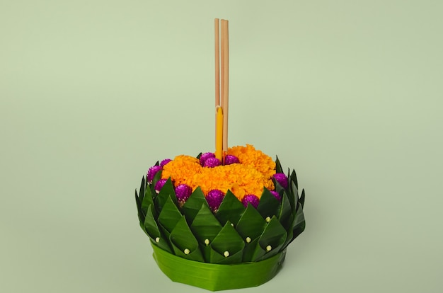 Banana leaf krathong that have 3 incense sticks and candle decorates with flowers for thailand full moon or loy krathong festival on green background.
