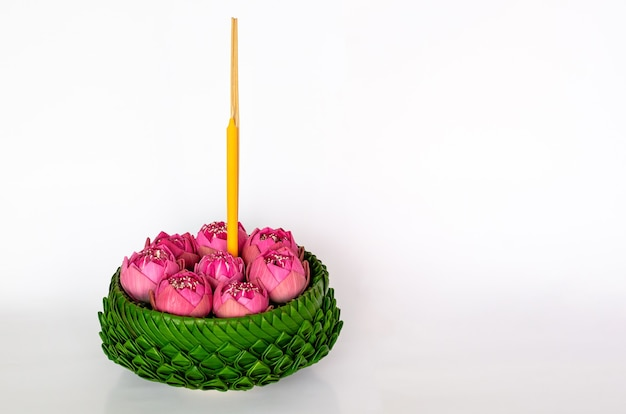 Banana leaf krathong that have 3 incense sticks and candle decorates with pink lotus flowers for thailand full moon or loy krathong festival isolated on white background.