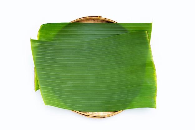 Banana leaves in bamboo basket on white background.