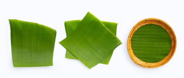 Банановые листья с бамбуковой корзиной на белом фоне.