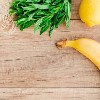Banana, lemon and mint on table