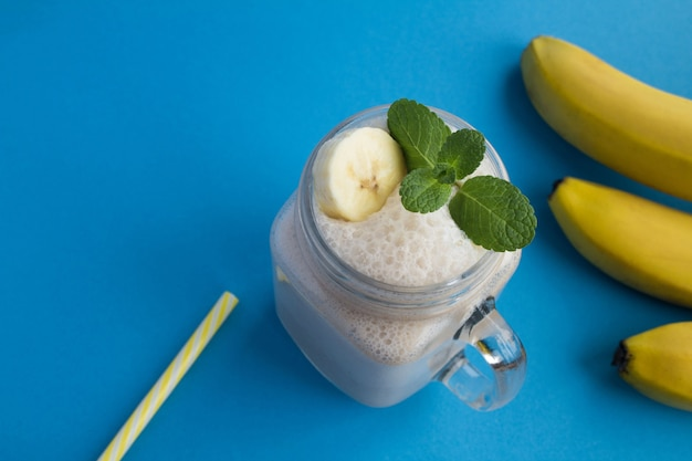 青い背景のガラスのバナナミルクセーキ。上面図。コピースペース。