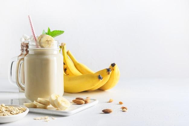 Banana milkshake on white board. vertical format