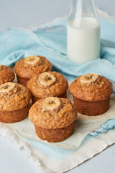 Banana muffin, side view, vertical. cupcakes on blue napkin with milk in bittle, white table