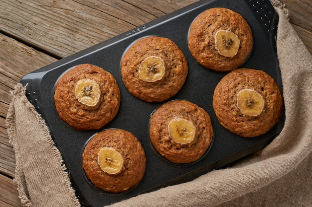 Banana muffin  in tray, top view. cupcakes on old linen napkin, rustic wooden table