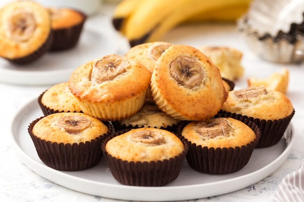 Banana muffins on a white plate. sweet cupcakes with slice of fruit.