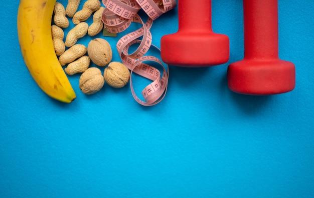 Банан, орехи, измерительная лента и гантели на синей стене. еда и фитнес-оборудование для здорового образа жизни