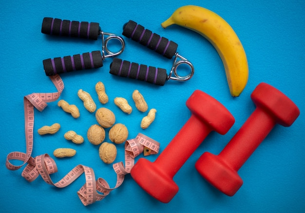 Банан, орехи, рулетка, усилитель захвата рук и гантели на синей стене. еда и фитнес-оборудование для здорового образа жизни