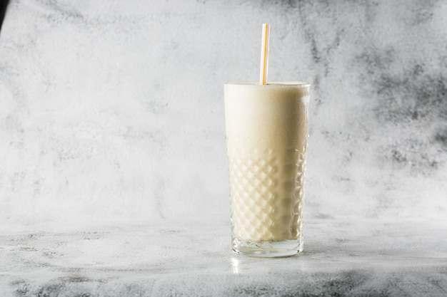 Banana oats smoothie or vanilla milkshake in glass on bright marble background. overhead view, copy space. advertising for milkshake cafe menu. horizontal photo.