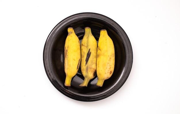 Банан на тарелке, изолированные на белом фоне