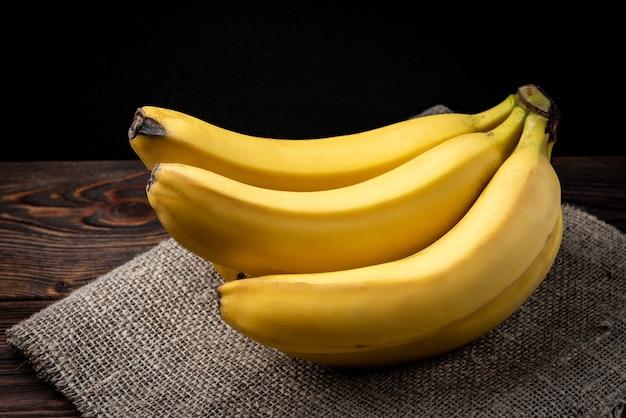 Банан на темном деревянном столе.