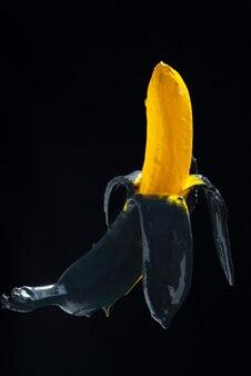 바나나 페인트. 검정색 배경 공중에 떠 있는 노란색-검정색 바나나