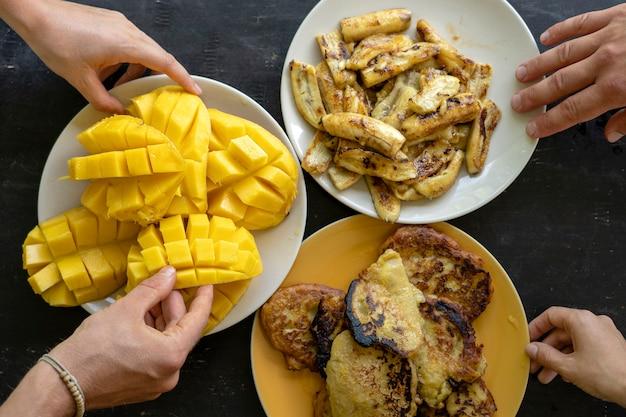 バナナのパンケーキ、揚げバナナ、黄色いマンゴー、そして人々の手。おいしいデザート、クローズアップ、上面図。おいしい料理を食べ、パーティーやコミュニケーションを楽しんでいる幸せな友達のグループ