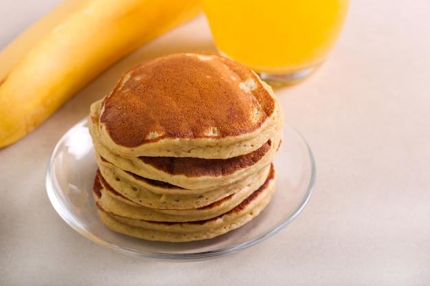 Банановые оладьи на тарелке и апельсиновый сок