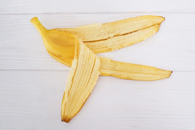 Banana peel on a white wooden background.