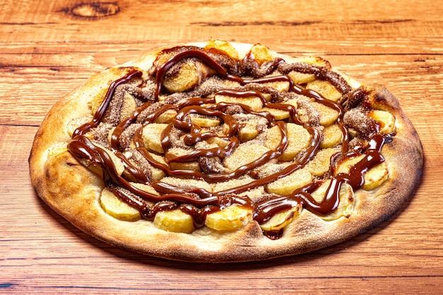 木製のテーブルにチョコレートソースとシナモンパウダーを添えたバナナピザ