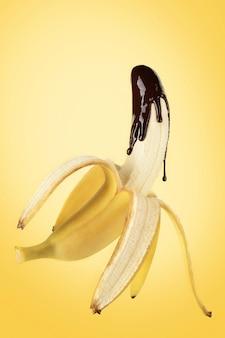 黄色の背景に液体チョコレートを注いだバナナ