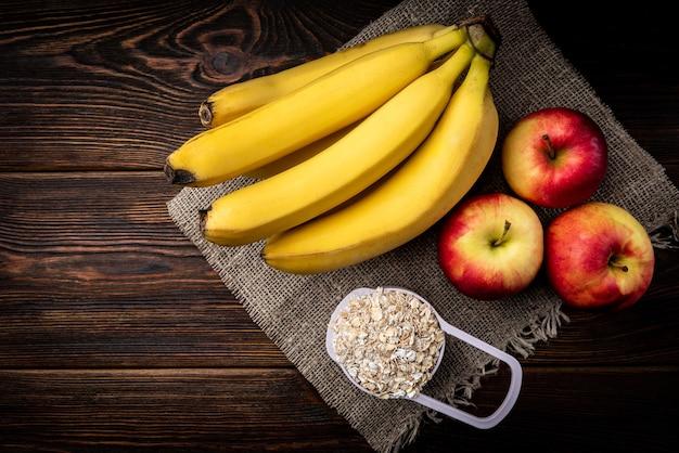 Банан, красные яблоки и овсяные хлопья на темном деревянном фоне.