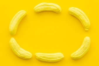 Banana shaped candies forming frame on yellow background