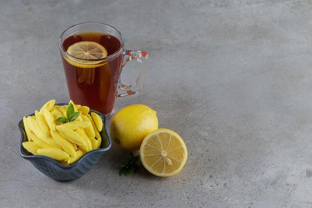 뜨거운 차와 신선한 레몬의 유리 컵과 바나나 모양의 씹는 사탕