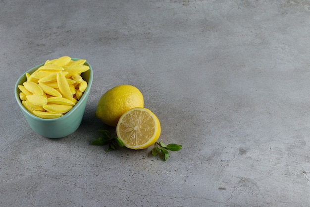 Banana shaped chewing candy with fresh lemon and mint leaves