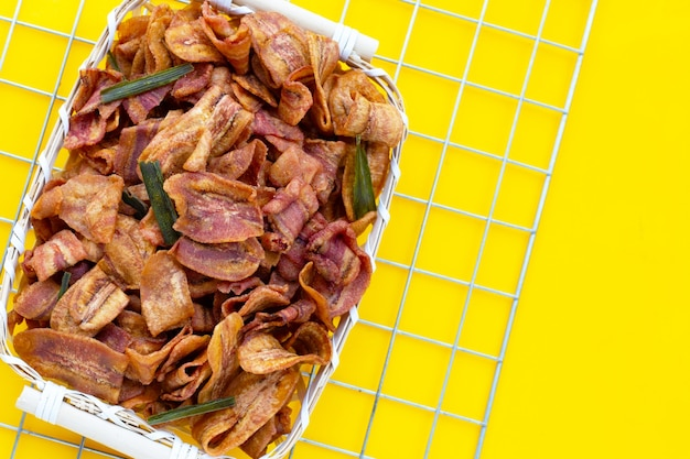 Banana slice chips in bamboo basket on yellow background.