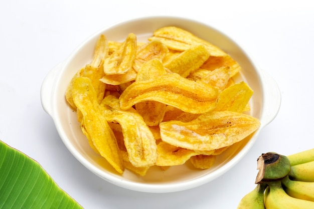 Banana slice chips in bowl on white background