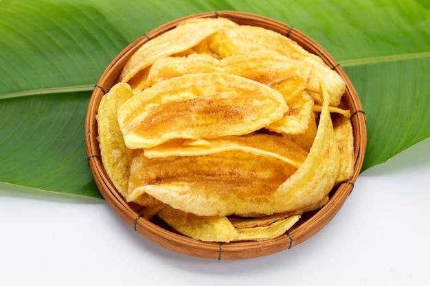 Обломоки ломтика банана в бамбуковой корзине на зеленых листах и белой предпосылке.