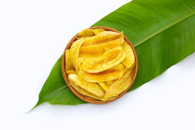 흰색 바탕에 녹색 잎에 대나무 바구니에 바나나 슬라이스 칩.