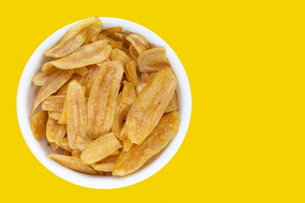Обломоки ломтика банана в белой тарелке на желтом фоне.