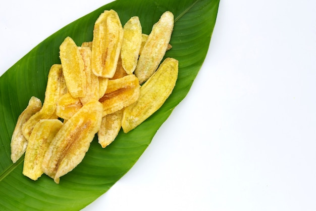 白い背景の上の緑の葉にバナナスライスチップ
