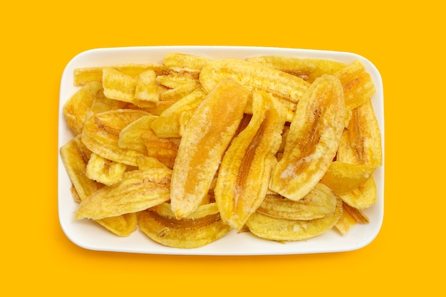 Banana slice chips in white plate on yellow background