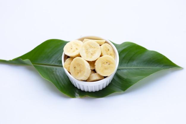 Ломтики банана в белой керамической чашке на зеленом листе