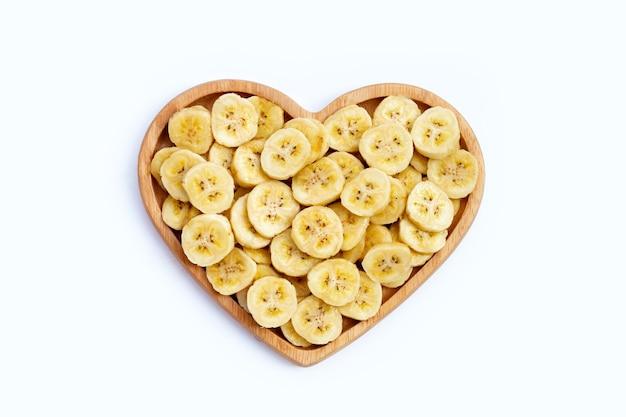 Ломтики банана в деревянной тарелке на белой поверхности