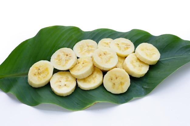 Ломтики банана на зеленом листе на белом фоне.