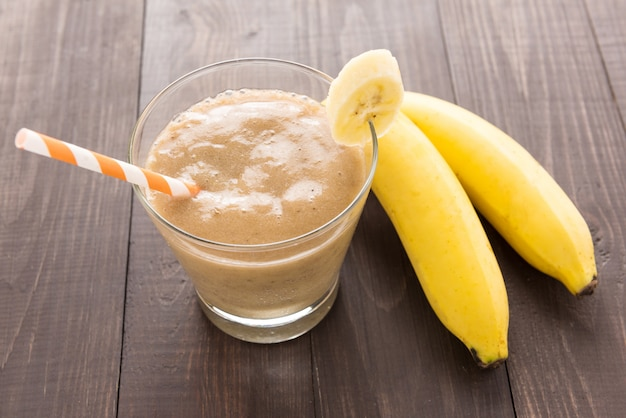 Banana smoothie and fresh banana on wooden background