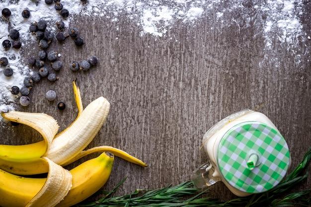 Banana smoothie and fresh banana on wooden table