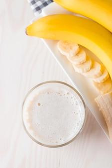 木製のテーブルにバナナのスムージー。