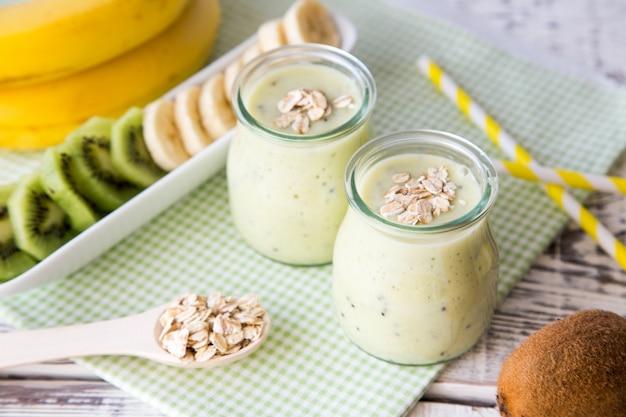 キウイとオート麦の軽い木製のテーブルの上にバナナのスムージー。タンパク質ダイエット健康食品のコンセプトです。