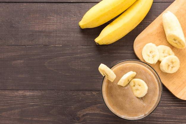 Banana smoothie on wooden background. top view