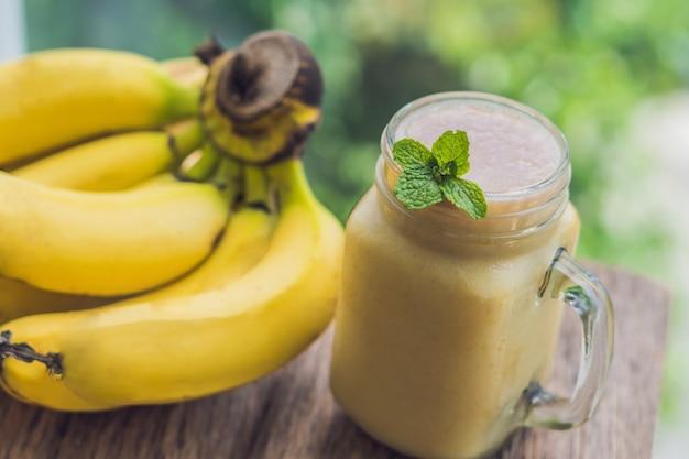 古い木製の背景にバナナのスムージーとバナナ。