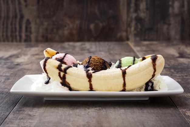 Banana split ice cream dessert with chocolate syrup on wooden