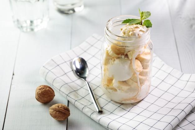 Banana split with vegan ice cream served in glass jar